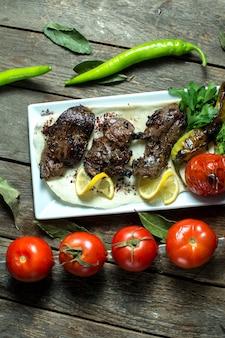 Top kebab de ternera servido con cebolla tomate a la parrilla y pimiento en fuente