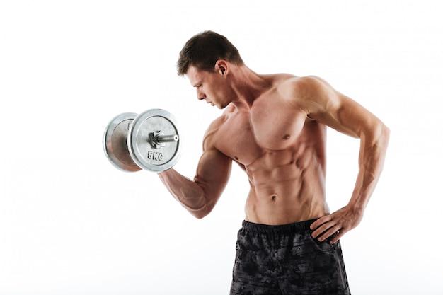 Topless joven atlético trabajando con pesas pesadas