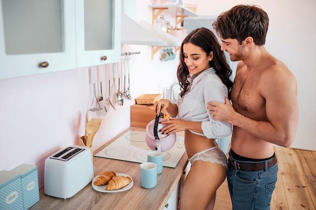 Topless joven parado en la cocina detrás de la mujer. él se inclina hacia ella y toma las manos de los antebrazos. modelo femenino vierta agua en tazas. ella sonríe.