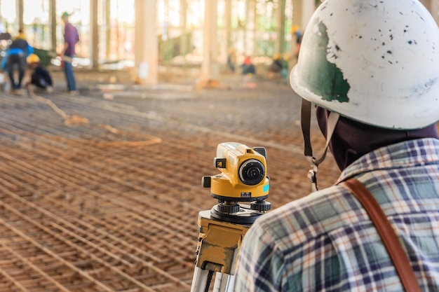 El topógrafo realiza mediciones con equipos de teodolito en el sitio de construcción de la fábrica.