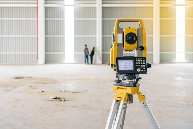Topógrafo tacómetro o teodolito equipo al aire libre en el sitio de construcción