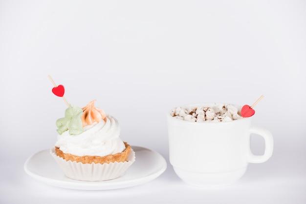 Toppers de corazón en cupcake y taza de café.