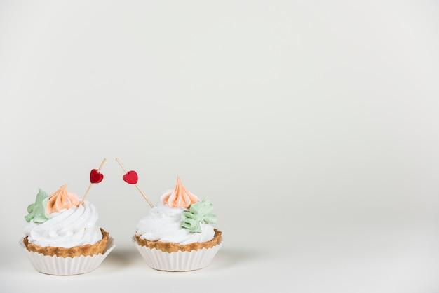 Toppers de corazón en dos cupcakes en la mesa