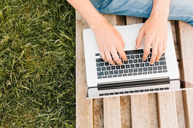 Topview hombre escribiendo en la computadora portátil en el parque