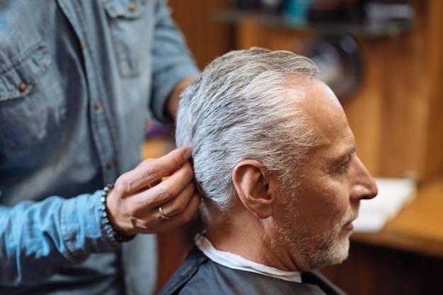 Toques perfectos. vista lateral del peluquero masculino acabado de peinado del visitante de peluquería senior.