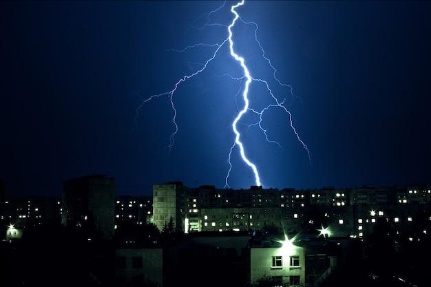 Tormenta de truenos y relámpagos nocturnos sobre los edificios