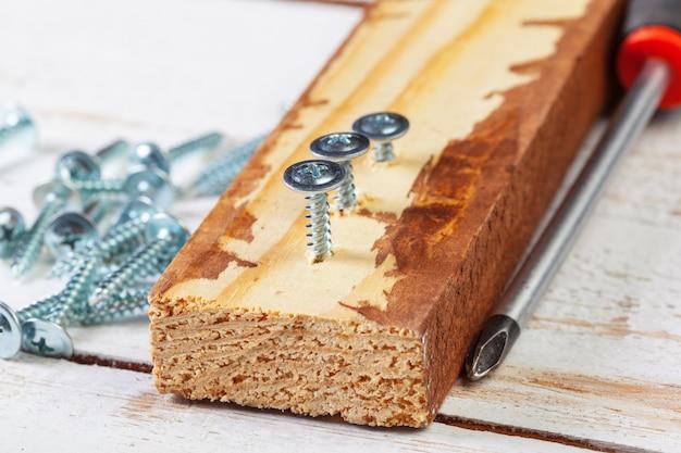 Tornillo atornillado en una barra de madera.