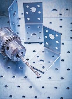 Tornillos de acero inoxidable perforados y broca metálica en concepto de construcción de chapa metálica perforada
