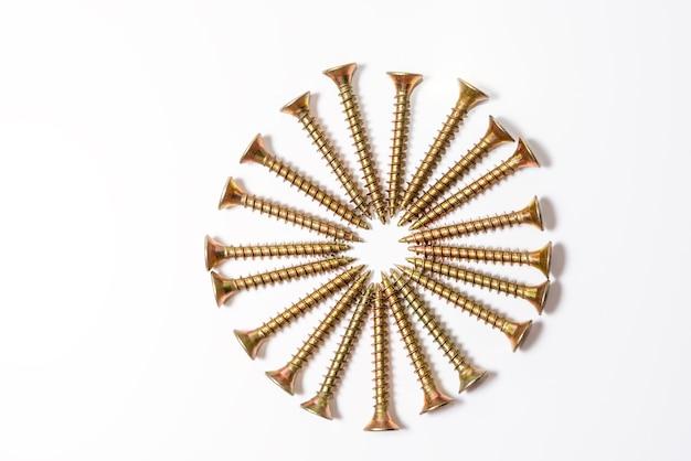 Los tornillos dorados están dispuestos en círculo sobre un fondo blanco. vista superior de tornillos de cabeza de zinc amarillo