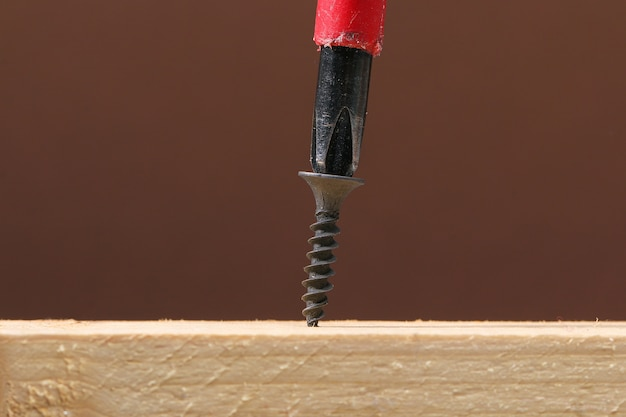 Tornillos de hierro negro atornillados en madera con un destornillador. sujetadores y herrajes.