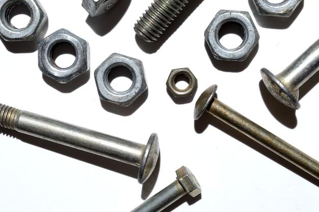Los tornillos y tuercas de diferentes tamaños se encuentran sobre un fondo blanco. vista superior.