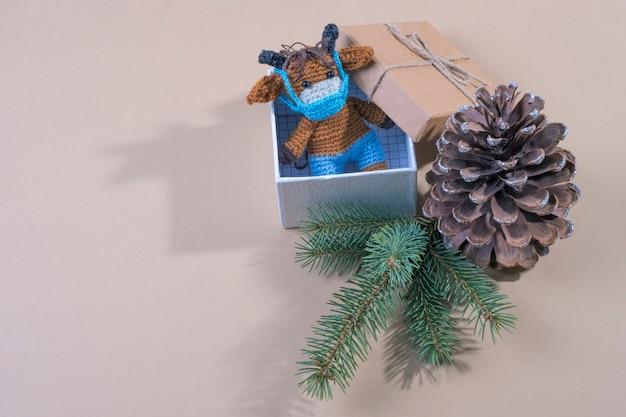 Toro de juguete de punto en la mascarilla en una caja de regalo. el concepto de navidad en la pandemia. espacio para texto