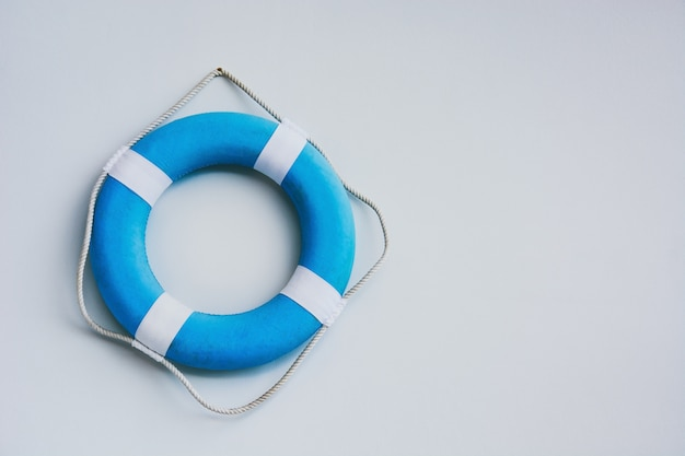 Toro de seguridad azul y blanco o salvavidas colgando en el fondo de la pared blanca, espacio de copia