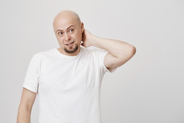Torpe hombre calvo de mediana edad se rasca el cuello y se ve desconcertado