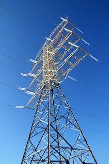 Torre alta eléctrica de cielo azul.