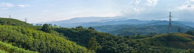 Torre de alta tensión y montaña en bosque