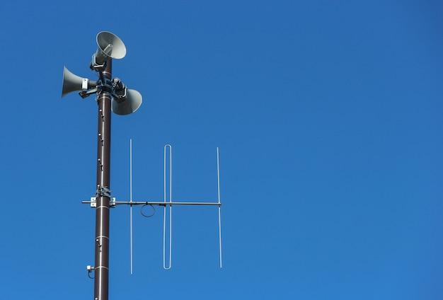 Torre de altavoces de seguridad para advertencia o anuncio con fondo de cielo azul claro