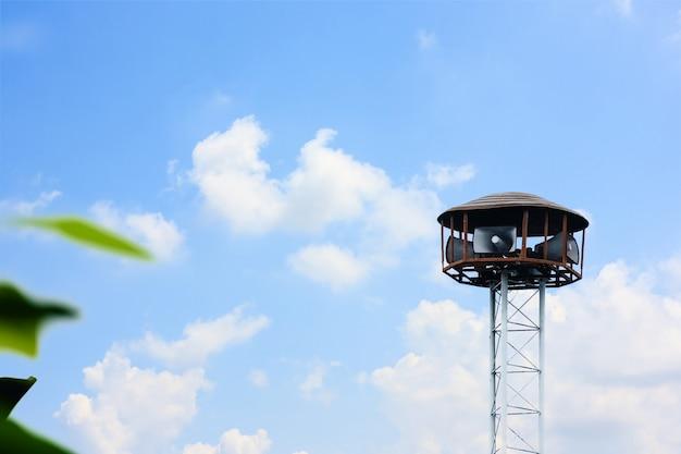 Torre del altavoz público contra el fondo del cielo nublado y azul