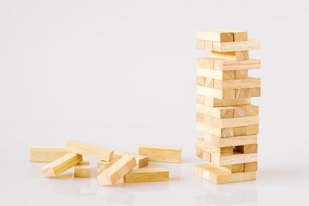 Torre de bloques de madera aislada en el fondo blanco con el espacio de la copia.