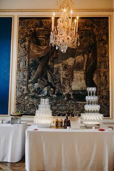Torre de cristal llena de champaña en el fondo de mosaico