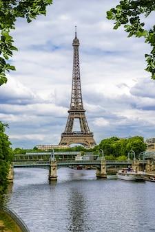 Torre eiffel en el fondo del río sena rodeada de hojas. parís. francia.