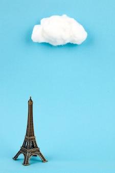 Torre eiffel en miniatura y cúmulos sobre fondo azul cielo