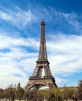 Torre eiffel en parís francia contra el cielo azul con nubes de abril