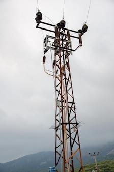 Torre eléctrica en las montañas, envuelta en niebla