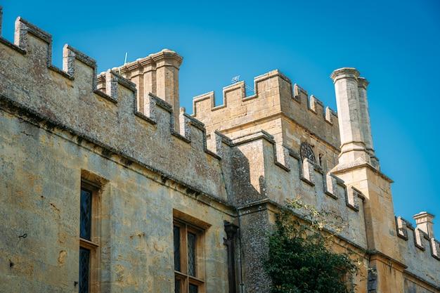 Torre y fachada de un castillo con día soleado y cielo azul