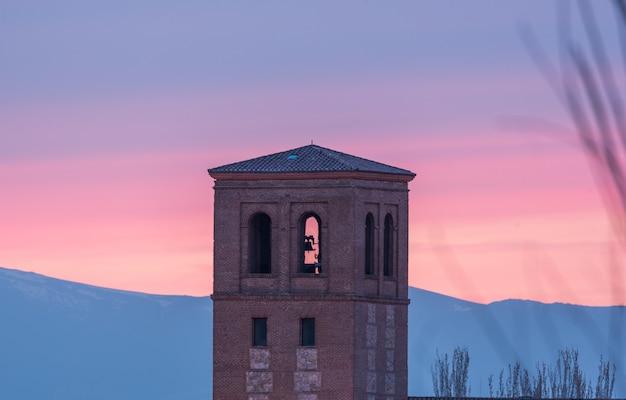 Torre de una iglesia al atardecer con montañas