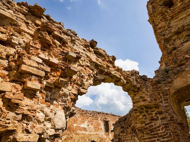 Torre de ladrillos viejos desmoronados y muros de la fortaleza, arcos de ladrillos viejos hechos de ladrillo rojo, todo el edificio está sujeto a destrucción y daños