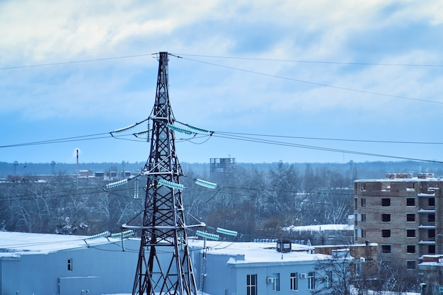 Torre de línea de transmisión de energía con aislantes de alto voltaje cubiertos de nieve. tiempo de invierno
