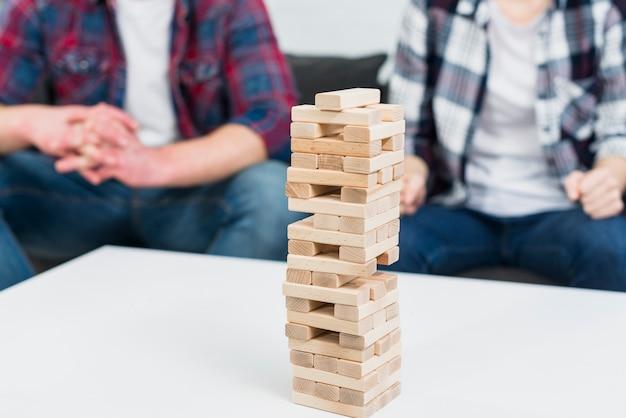 Torre de madera del bloque en la tabla blanca delante de los pares que se sientan en el sofá
