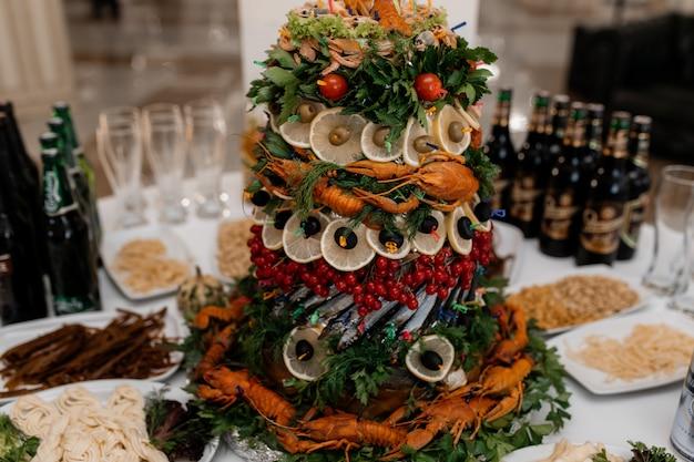 Torre de mariscos, camarones, vegetación y cangrejos de río en la deliciosa mesa buffet