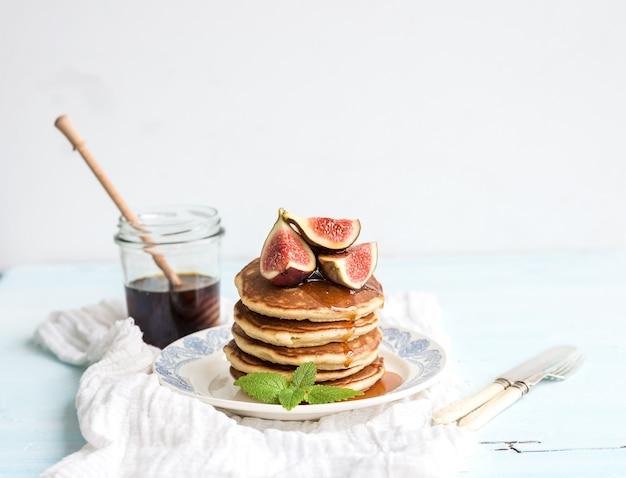 Torre de panqueques con higos frescos y miel en un plato rústico. mesa blanca