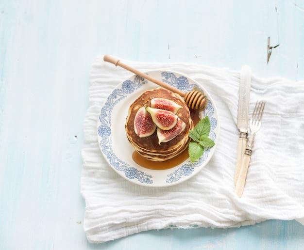 Torre de panqueques con higos frescos y miel en un plato rústico. superficie azul claro