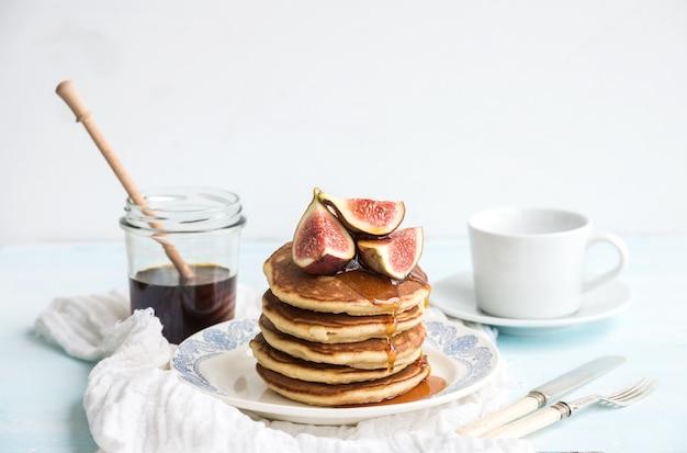 Torre de panqueques con higos frescos y miel en un plato rústico. superficie blanca