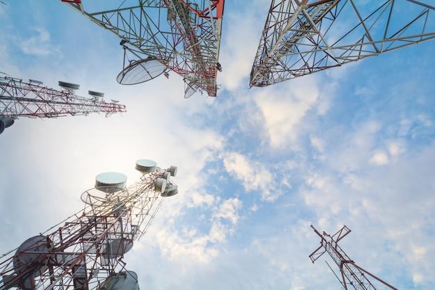 Torre de la telecomunicación con las antenas con el cielo azul en la luz del sol de la mañana.