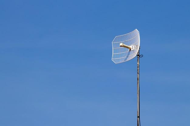 Torre de telecomunicaciones con cielo azul y nubes blancas, tecnología de comunicación de poste de satélite.