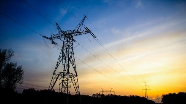 Torres de poder de transmisión de alta tensión silueta en la puesta del sol