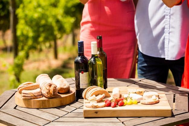 Torso de amigos por comida y botellas de vino en la mesa
