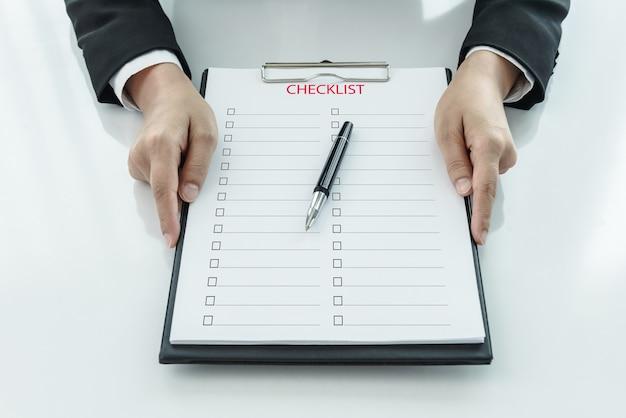 Torso de empresaria sosteniendo portapapeles con lista de verificación contra
