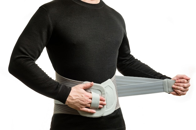 Torso de un hombre con un corsé ortopédico sobre un fondo blanco.