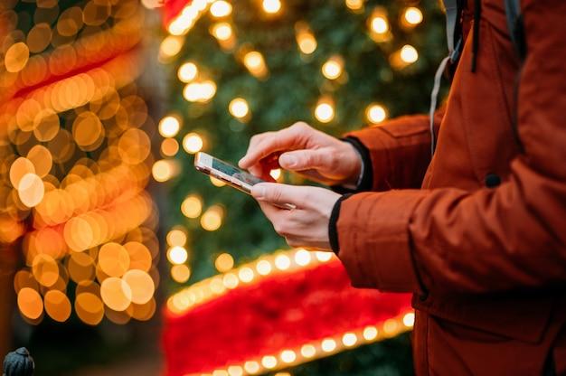 Torso del hombre con teléfono inteligente contra el árbol de navidad iluminado.