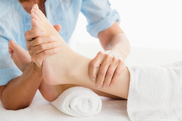 Torso de masajista dando masaje de pies a mujer
