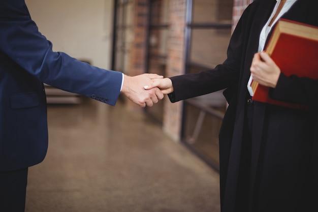 Torso de mujer abogado apretón de manos con cliente