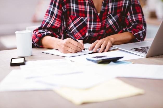 Torso de mujer escribiendo en el bloc de notas