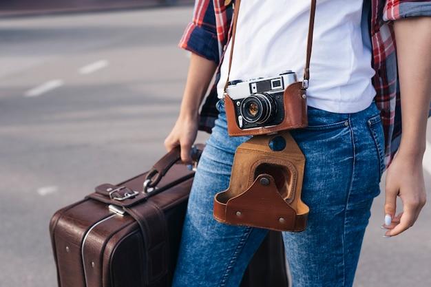 Torso de mujer joven viajero con bolsa de equipaje en la calle