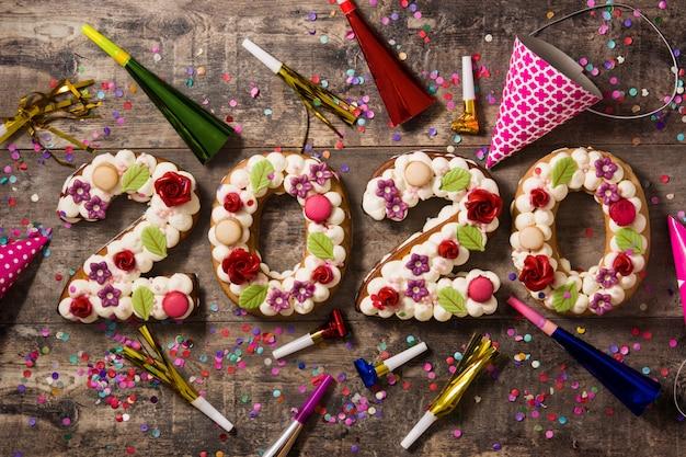 Torta 2020 y adornos en mesa de madera. concepto de año nuevo