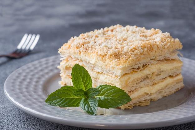 Torta acodada con milhojas de vainilla de napoleón crema rebanada con menta en la oscuridad